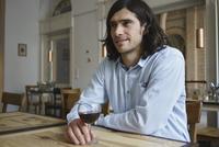 Smiling man having wine while sitting at cafe