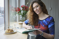 Portrait of smiling woman reading book while having breakfast at cafe