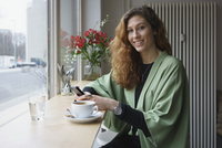 Portrait of young woman holding phone and having coffee at cafe