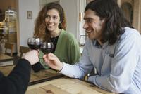 Happy friends drinking wine while sitting at cafe 11016032236| 写真素材・ストックフォト・画像・イラスト素材|アマナイメージズ