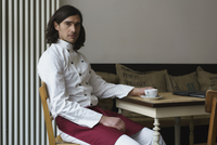 Portrait of confident chef having coffee at cafe