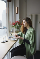 Thoughtful woman using laptop while having coffee at cafe