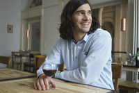 Happy man having wine while sitting at cafe