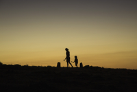 Silhouette woman and boy walking on field against clear sky during sunset