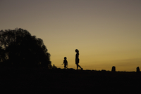 Silhouette boy and woman walking on field against clear sky during sunset