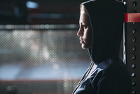 Close-up side view of woman wearing hooded shirt standing at gym
