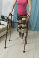 Low section of disabled woman walking with mobility walker at home