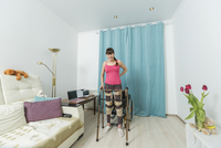 Portrait of happy disabled woman standing with mobility walker at home