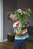 Happy boy holding bunch of flowers standing at home