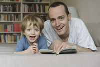 Portrait of smiling father and son lying on bed with book at home