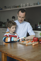 Father looking at son chopping carrot on table at kitchen