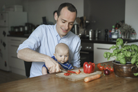 Father carrying son and chopping vegetables in kitchen