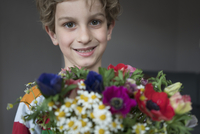 Close-up portrait of smiling boy holding bunch of flowers