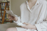 Midsection of woman reading prescription of pills at home