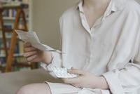 Midsection of woman reading prescription of pills at home 11016032514| 写真素材・ストックフォト・画像・イラスト素材|アマナイメージズ