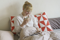 Smiling woman having coffee while using digital tablet on bed at home