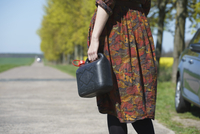 Midsection of young woman holding gas can while standing on road by car