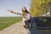 Cheerful woman sitting on car window at roadside