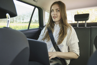 Portrait of businesswoman using laptop in car