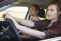 Woman driving while sitting besides man in car