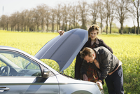 Woman looking at man repairing car by field