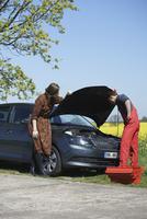 Woman looking at mechanic repairing car on roadside