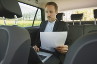 Businessman holding document while using laptop in car