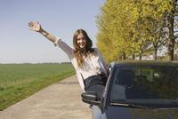 Portrait of cheerful woman sitting on car window at roadside