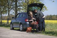 Woman sitting in car trunk besides man on roadside