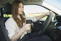 Businesswoman holding insulated drink container while driving car