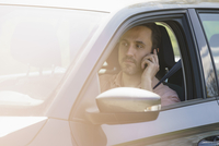 Man talking on mobile phone while driving car on sunny day
