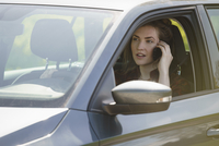 Woman talking on mobile phone while driving car on sunny day