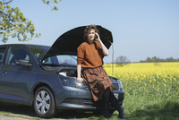 Woman talking on phone while sitting on open car hood at roadside