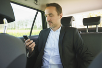Businessman using phone while traveling in car