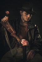 Thoughtful cowboy holding rose and rifle over gray background