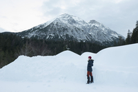 Woman standing on snow covered field against mountains