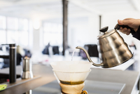Cropped image of person pouring water into filter coffee maker