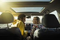 Rear view of happy couple looking at each other in car
