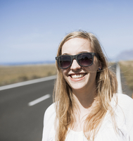 Smiling young woman wearing sunglasses on road