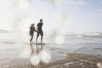 Full length of happy couple running in sea