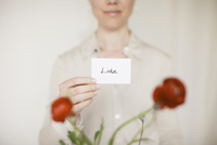 Midsection of mid adult woman holding love sign in front of red flowers