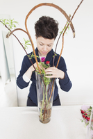 Mid adult woman arranging flowers in vase on table at home