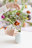 Cropped image of woman arranging flowers in vase on table at home
