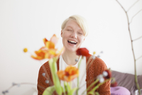 Cheerful mid adult woman with flowers in foreground at home
