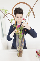 Mid adult woman arranging flowers in glass vase on table at home