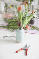 Pruning shears by vase with woman arranging flowers in background at home