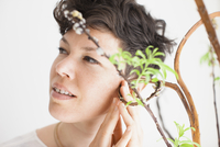 Mid adult woman feeling plant against white background