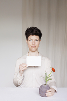 Portrait of mid adult woman holding blank card and flower vase at table