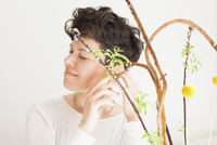 Happy mid adult woman feeling plant against white background
