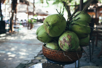 Fresh coconuts in basket outdoors
